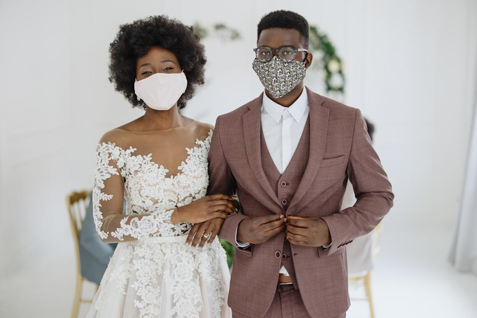 Young newlywed Black couple wears face protective masks at the reception of their wedding