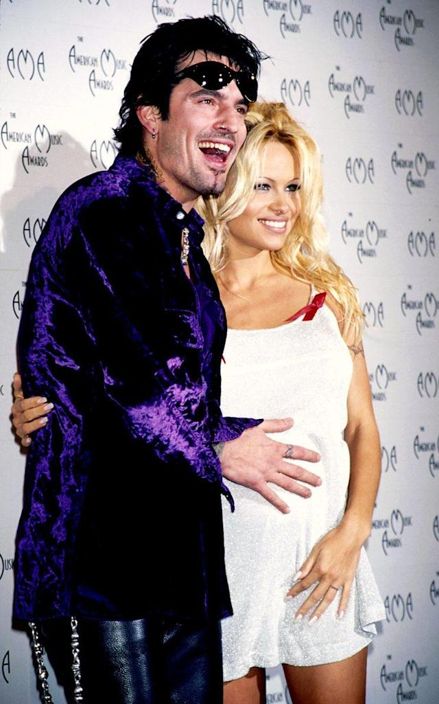 A pregnant Pamela Anderson and Tommy Lee pose on the red carpet. (Photo: Kevin Mazur/WireImage)