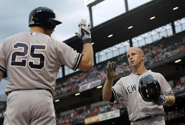 New York Yankees left fielder Brett Gardner, right, greets teammate Mark Teixeira after scoring on a sacrifice ground ball by Derek Jeter in the first inning of a baseball game against the Baltimore Orioles, Monday, Aug. 11, 2014, in Baltimore. (AP Photo/Patrick Semansky)