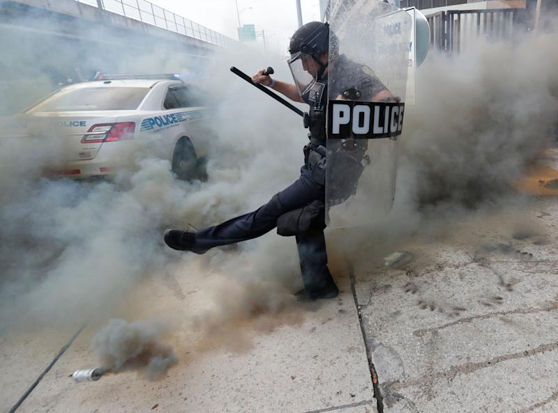A policeman kicks back a tear gas canister during a demonstration next to the city of Miami Police Department on May 30, 2020.