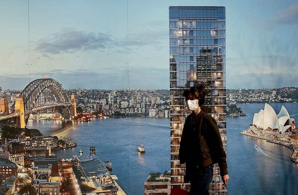 A masked woman walking past a poster of Sydney harbour during the city's ongoing lockdown. Source: Getty