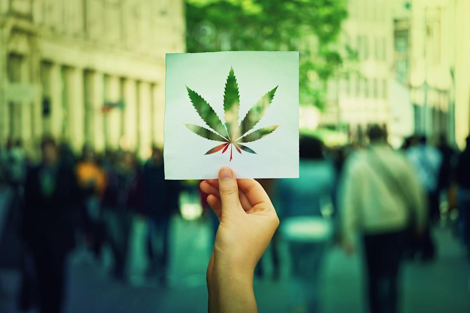 A hand holding a piece of paper with a cannabis leaf cut out and pedestrians in a city in the background.