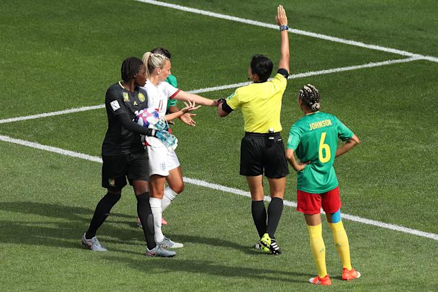 Toni Duggan of England shows referee Qin Liang phlegm on her arm after she is spat on by Augustine Ejangue. (Photo by Charlotte Wilson/Offside/Offside via Getty Images)