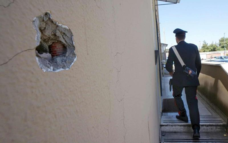 A bullet hole in the wall of a police station in Naples, after it was sprayed with rounds from a Kalashnikov assault rifle by suspected Camorra criminals. - Credit: ANSA