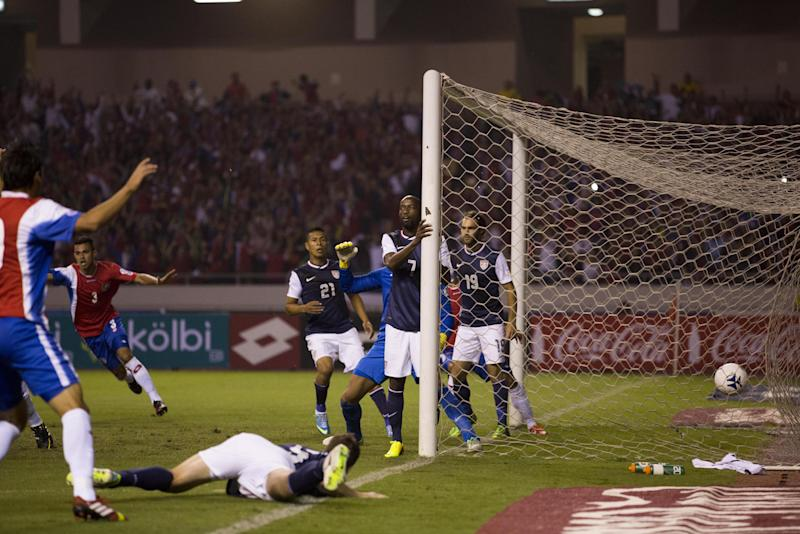 U.S.' players stand by the goal post after Costa Rica's Jonhy Acosta, behind left, scored against them at a 2014 World Cup qualifier soccer match in San Jose, Costa Rica, Friday, Sept. 6, 2013. (AP Photo/Moises Castillo)