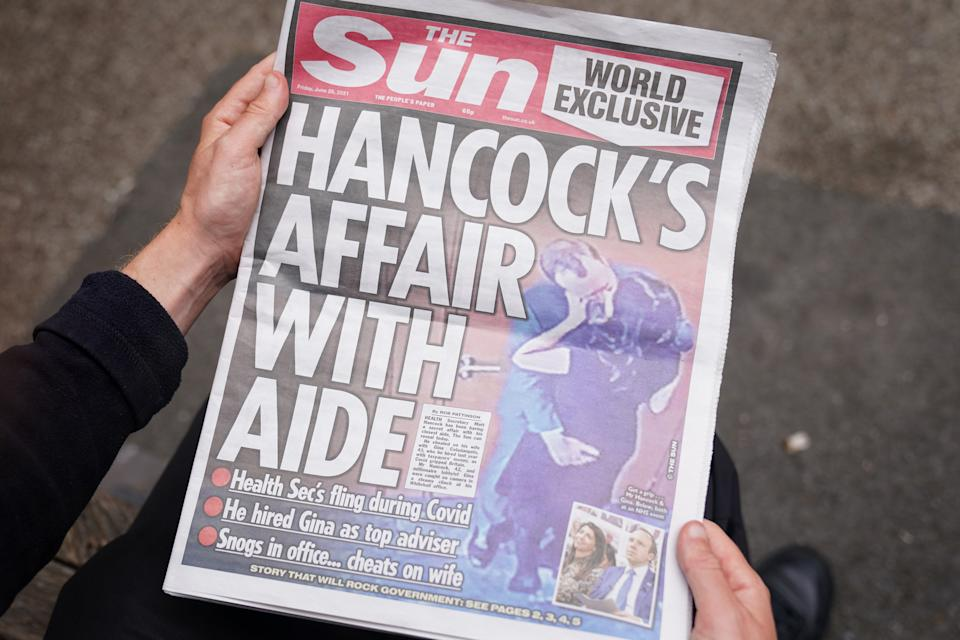 A person reads a copy of the Sun newspaper in Westminster, London, with the story and pictures of Health Secretary Matt Hancock appearing to kiss his adviser Gina Coladangelo, who the newspaper said was hired by Mr Hancock last year. Picture date: Friday June 25, 2021. (Photo by Kirsty O'Connor/PA Images via Getty Images)