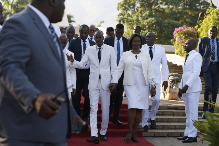 Accompanied by First Lady Martine Moise, center right, and and acting prime minister Jean Michel Lapin, center left, President Jovenel Moise, center, arrives to lay flowers to mark the anniversary of the death of Haitian revolution leader Jean Jacques Dessalines, at Champ de Mars, adjacent to the National Palace, in Port-au-Prince, Haiti, Thursday Oct. 17, 2019. President Moise has been facing ever more violent protests demanding his resignation fueled by anger over corruption, inflation and dwindling of basic supplies, including gasoline. (AP Photo/Rebecca Blackwell)