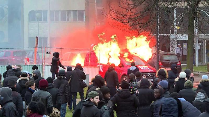 Image grab taken from an AFPTV video shows a van of radio station RTL burning during clashes on the edge of a rally in Bobigny, outside Paris on February 11, 2017 to denounce police brutality after a black man was allegedly raped