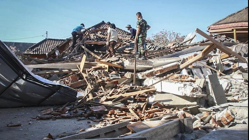 Rescuers search for victims in a collapsed house after a quake struck Indonesia's island of Lombok