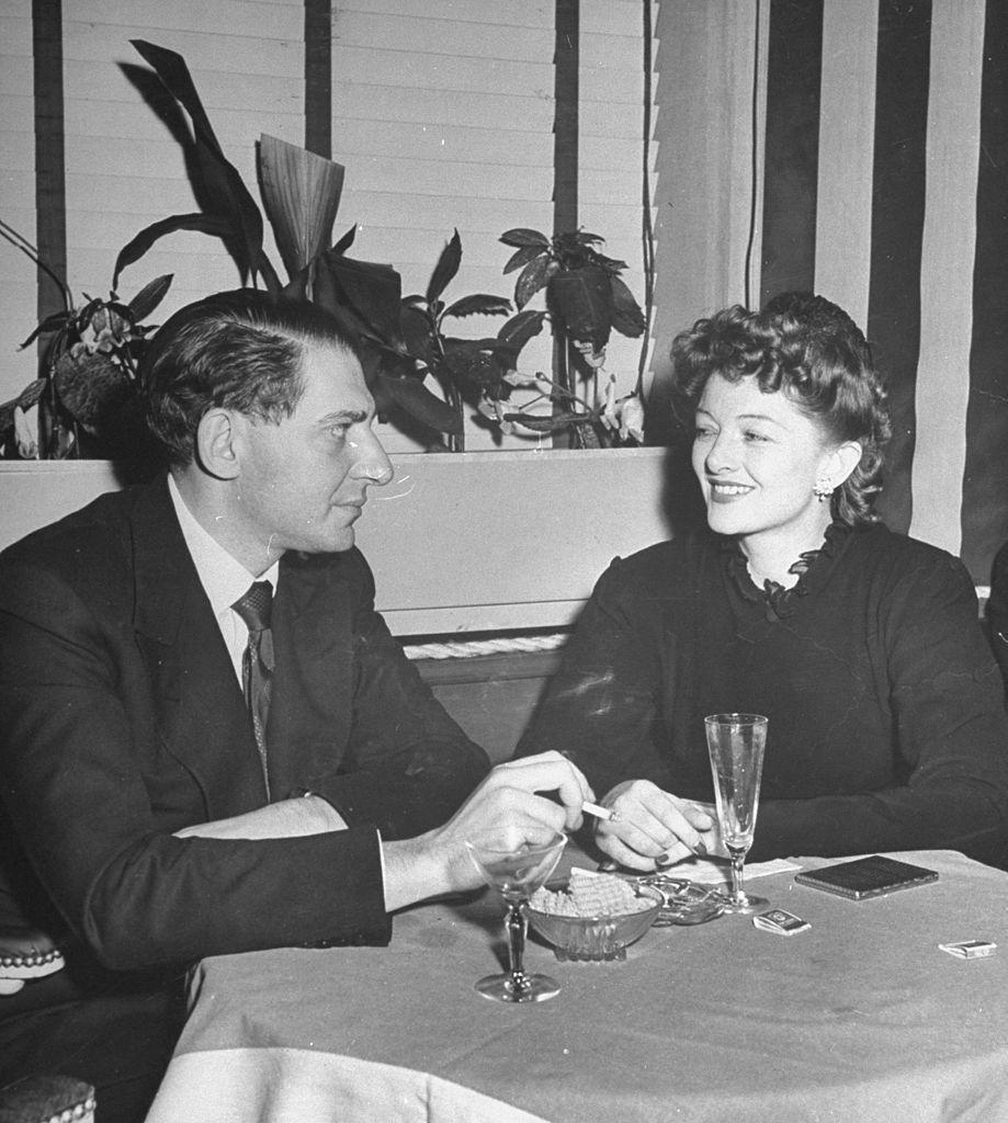 <p>John Hertz Jr. and his wife, actress Myrna Loy, share drinks in New York City. </p><p>Other celebrity visitors this year: Frank Sinatra, Irving Berlin.<br></p>