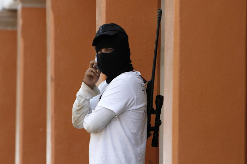 In this May 20, 2013 photo, a masked and armed man belonging to a local self-defense group stands guard in the town of Cuemalco, Mexico. Self-defense groups started to spring up in February to fight back the Knights Templar drug cartel which is extorting protection payments from cattlemen and lime growers, butchers and even marijuana growers. The federal government sees both the self-defense forces and the cartel as dangerous enemies. (AP Photo/Marco Ugarte)