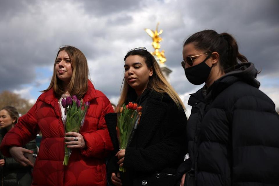 Members of the public hold flowers outside Buckingham Palace