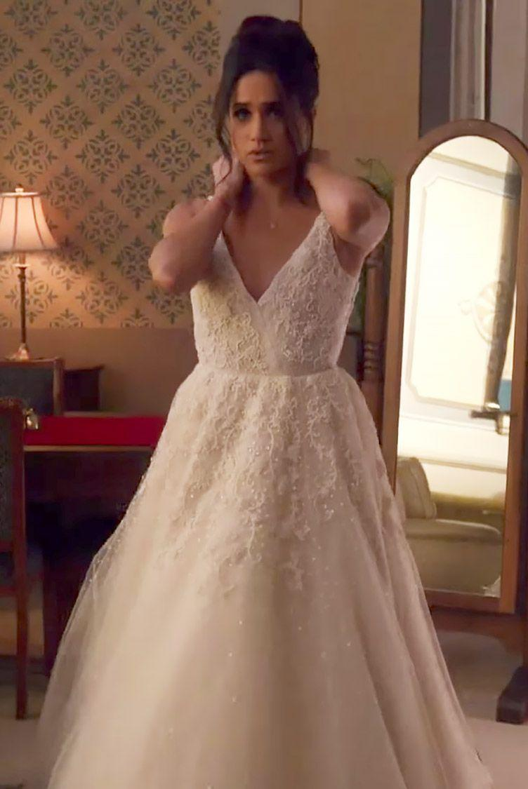 """<p>Rachel Zane (played by Meghan Markle, obvi) wore a <a href=""""https://www.cosmopolitan.com/entertainment/celebs/a19644230/meghan-markle-suits-wedding-dress/"""" rel=""""nofollow noopener"""" target=""""_blank"""" data-ylk=""""slk:V-neck dress with a fitted waist and floral appliqués"""" class=""""link rapid-noclick-resp"""">V-neck dress with a fitted waist and floral appliqués</a> in the season 7 finale when she (finally!) marries Mike Ross. The dress, <a href=""""https://www.brides.com/gallery/new-anne-barge-wedding-dresses-spring-2019"""" rel=""""nofollow noopener"""" target=""""_blank"""" data-ylk=""""slk:designed by Anne Barge"""" class=""""link rapid-noclick-resp"""">designed by Anne Barge</a>, was vastly different from <a href=""""https://www.cosmopolitan.com/style-beauty/fashion/a19694897/meghan-markle-dress-royal-wedding/"""" rel=""""nofollow noopener"""" target=""""_blank"""" data-ylk=""""slk:Meghan's IRL wedding gown"""" class=""""link rapid-noclick-resp"""">Meghan's IRL wedding gown</a>, which was an off-the-shoulder style with three-quarter length sleeves. </p>"""