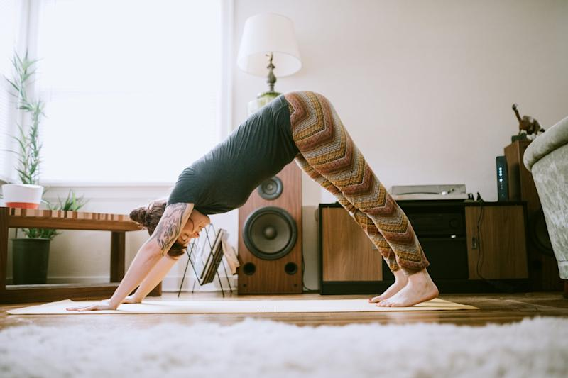 A cheerful woman enjoys performing yoga stretches and exercise routines in her living room, the sun shining brightly through the windows.