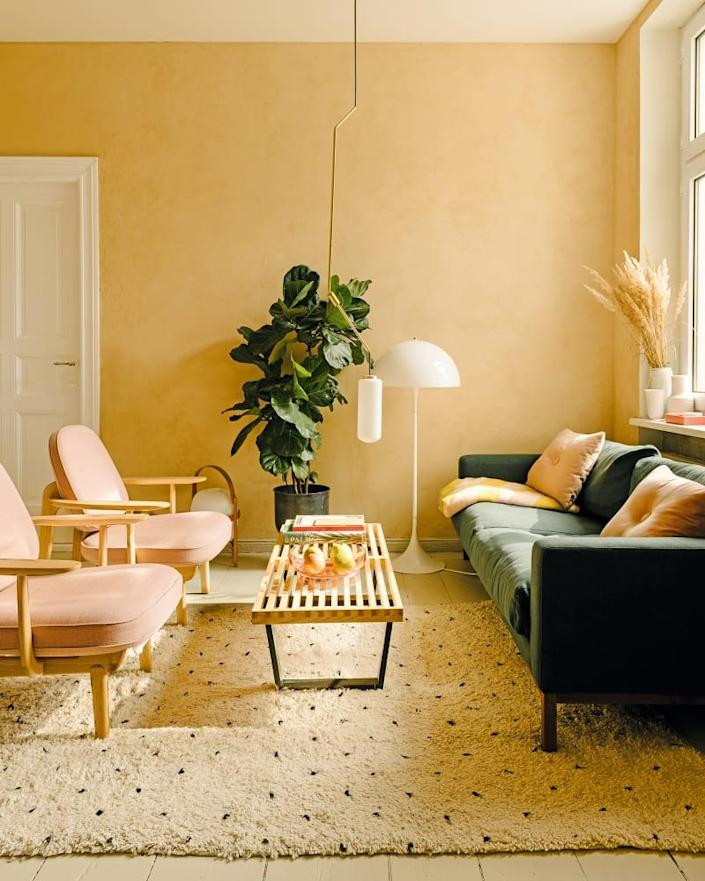 The walls in the living room are painted in clay from Nen-Do. Jaime Hayon's Fred armchairs and a Bolia sofa flank George Nelson's bench for Vitra. The floor lamp is by Louis Poulsen.