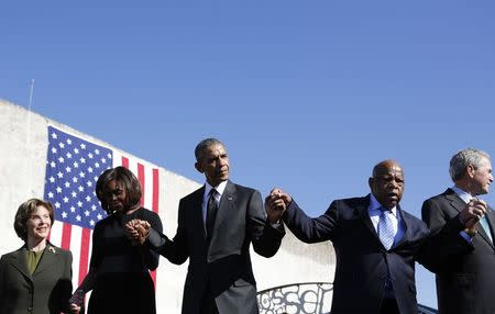 U.S. President Barack Obama and first lady Michelle Obama (2nd L) hold hands with former President George W Bush (R) and former first lady Laura Bush (L) and U.S. Rep. John Lewis (D-GA) during commemoration of the 50th anniversary of the 'Bloody Sunday' historical civil rights march at the Edmund Pettus Bridge in Selma, Alabama, March 7, 2015. REUTERS/Jonathan Ernst