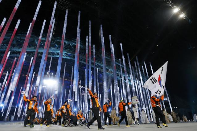 South Korea's flag-bearer Jung Seung-Hwan (R), leads his country's contingent during the opening ceremony of the 2014 Paralympic Winter Games in Sochi, March 7, 2014. REUTERS/Alexander Demianchuk (RUSSIA - Tags: OLYMPICS SPORT)