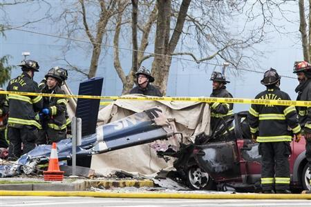 Firefighters investigate the crash of a KOMO News helicopter, which killed KOMO news photographer Bill Strothman and pilot Gary Fitzner near the Space Needle, in Seattle