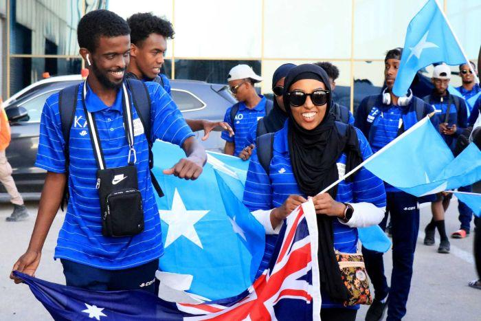 Amina Liban walking with other African-Australians holding an Australian flag.