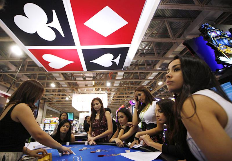 FILE - In this May 22, 2012 file photo, attendants learn poker at a gambling table at Gaming Expo Asia in Macau. In the Philippines, a $4 billion casino project will soon rise from reclaimed land on Manila Bay. In South Korea, foreign investors will break ground next year on a clutch of casino resorts offshore. In the Philippines, a $4 billion casino project will soon rise from reclaimed land on Manila Bay. In South Korea, foreign investors will break ground next year on a clutch of casino resorts offshore. And on the eastern edge of Russia, authorities plan a resort zone aimed at drawing Chinese high-rollers. The projects are part of a casino building boom rolling across Asia, where governments are trying to develop their tourism markets to capture increasingly affluent Asians with a penchant for gambling. (AP Photo/Kin Cheung, File)