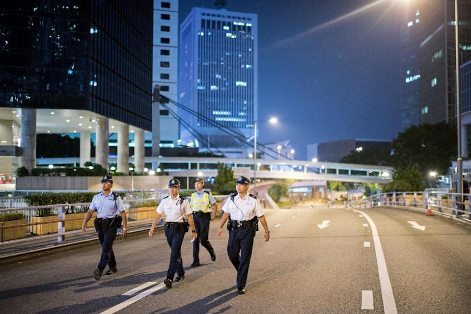 Police patrol an empty highway barricaded by pro-democracy protesters in Hong Kong on October 10, 2014 (AFP Photo/Alex Ogle)