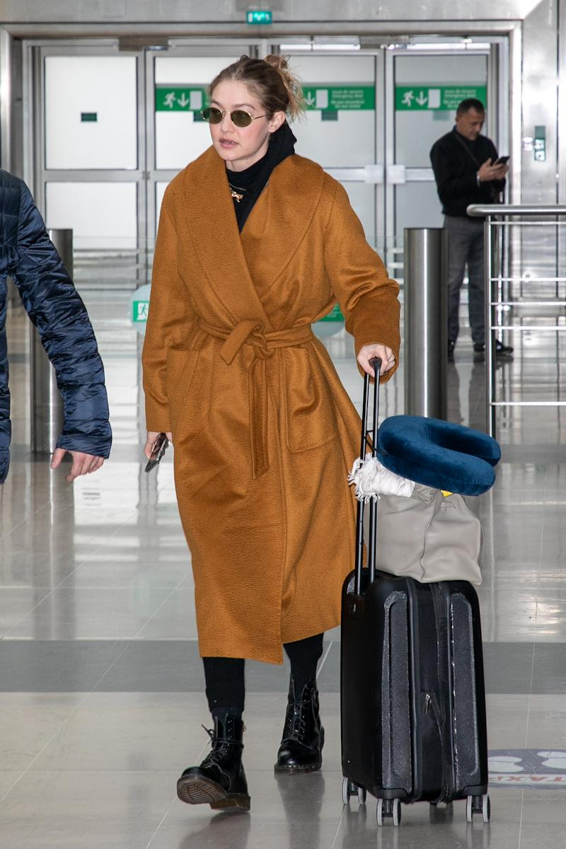 Gigi Hadid wears a wrap coat at Charles de Gaulle airport. (Credit: Getty Images)