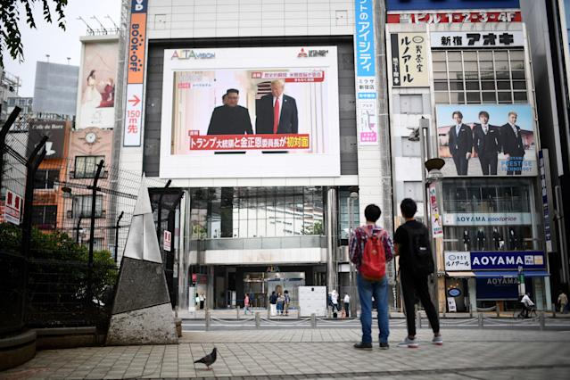 <p>Pedestrians look at a screen displaying live news of meeting between North Korean leader Kim Jong Un and US President Donald Trump, in Tokyo on June 12, 2018. – Donald Trump and Kim Jong Un have become on June 12 the first sitting US and North Korean leaders to meet, shake hands and negotiate to end a decades-old nuclear stand-off. (Photo: Martin Bureau/AFP/Getty Images) </p>