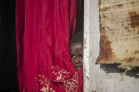 Jonelson Princeton, 7, who survived cholera as a newborn, peers out from inside his home which was once used as an office, on a former UN base where he lives with his parents and grandmother in Mirebalais, Haiti, Monday, Oct. 19, 2020. Ten years after a cholera epidemic swept through Haiti and killed thousands, families of victims still struggle financially and await compensation from the United Nations as many continue to drink from and bathe in a river that became ground zero for the waterborne disease. (AP Photo/Dieu Nalio Chery)
