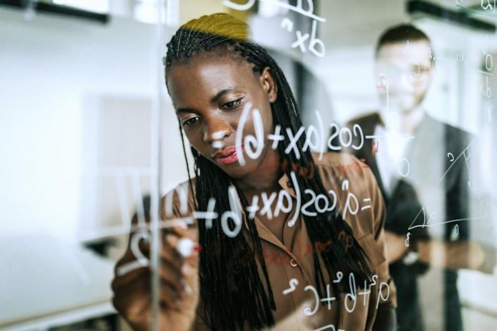 Black woman writing formulas on a board.