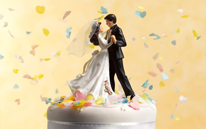 Bride and groom on a cake - Peter Dazeley/The Image Bank RF