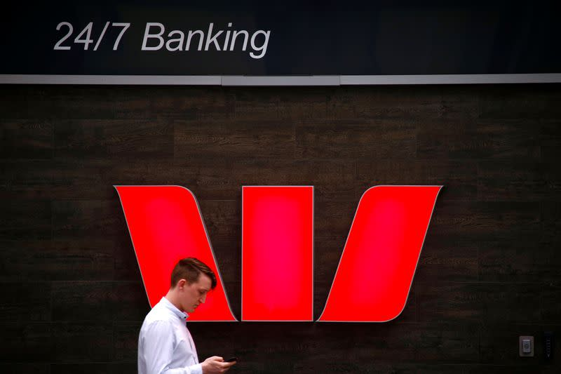A pedestrian looks at his phone as he walks past a logo for Australia's Westpac Banking Corp located outside a branch in central Sydney