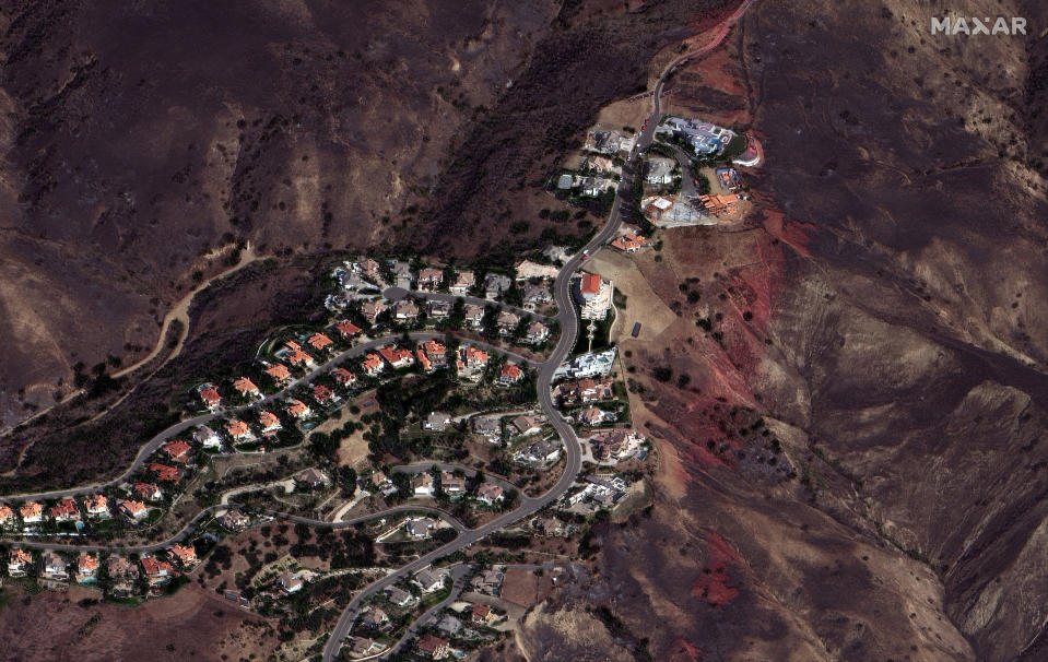 In a photo provided by Maxar Technologies, slurry dropped against the Blue Ridge Fire leaves a red trail to the right of homes in Yorba Linda, Calif., Wednesday, Oct. 28, 2020. Thousands of Californians were allowed to return to their homes Wednesday as calmer winds helped firefighters beat back two wind-driven wildfires that had spurred widespread evacuations. (Maxar Technologies via AP)