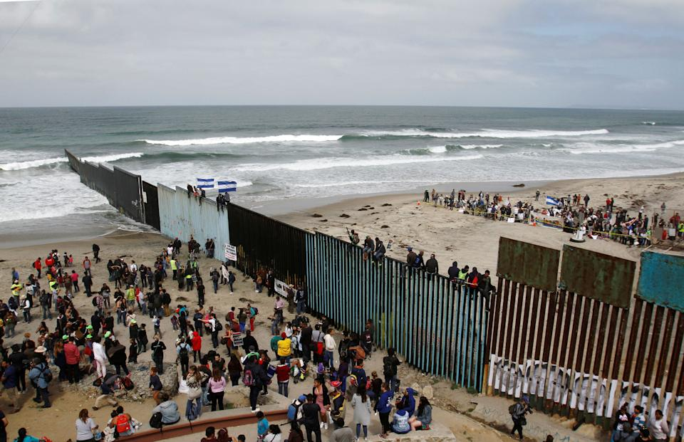 Members of a caravan of migrants from Central America and supporters gather on both sides of the border fence.