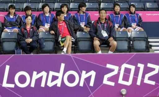 North Korea's coach Gun Sin Ui (C) waits for his team's delayed group G women's match