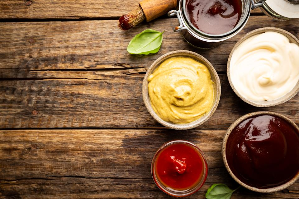 Classic set of sauces, American yellow mustard, ketchup, barbecue sauce, mayonnaise on wooden background, top view with copy space.