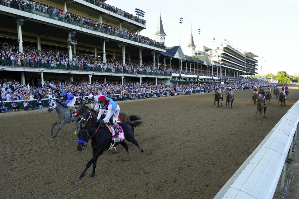 John Velazquez riding Medina Spirit leads Florent Geroux on Mandaloun, Flavien Prat riding Hot Rod Charlie and Luis Saez on Essential Quality to win the 147th running of the Kentucky Derby at Churchill Downs, Saturday, May 1, 2021, in Louisville, Ky. (AP Photo/Jeff Roberson)
