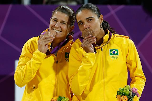 LONDON, ENGLAND - AUGUST 08: Bronze medallists Larissa Franca and Juliana Silva of Brazil celebrate on the podium during the medal ceremony for the Women's Beach Volleyball on Day 12 of the London 2012 Olympic Games at the Horse Guard's Parade on August 8, 2012 in London, England. (Photo by Jamie Squire/Getty Images)