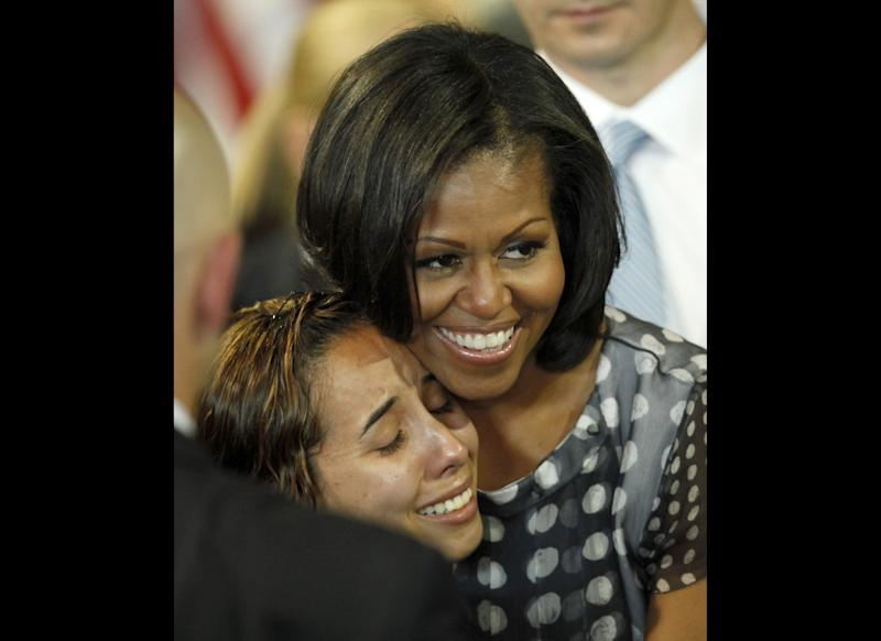 First lady Michelle Obama hugs a woman in the audience after Illinois Gov. Pat Quinn signed into law a measure allowing military personnel and their spouses a quicker transfer of their professional licenses to Illinois during a military relocation, Tuesday, June 26, 2012, in Chicago.