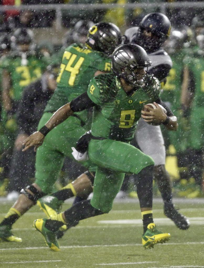 Oregon quarterback Marcus Mariota rushes during the first half of an NCAA college football game against California in Eugene, Ore., Saturday, Sept. 28, 2013. (AP Photo/Don Ryan)