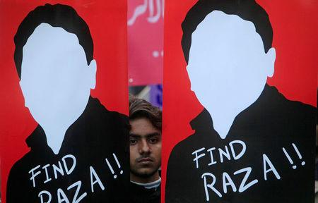 A demonstrator holds placards calling for the release of Raza Mehmood Khan, a member of Aghaz-i-Dosti (Start of Friendship), a group that works on peace building between Pakistan and India, during a protest in Lahore, Pakistan December 11, 2017.  REUTERS/Mohsin Raza