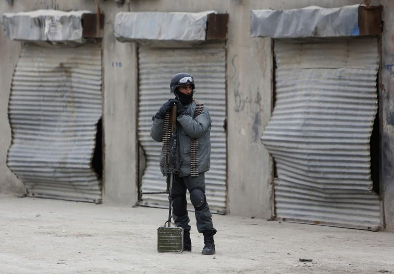 An Afghan policeman stands at the site of a bomb attack in Kabul