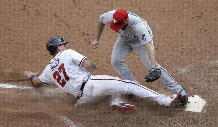Atlanta Braves' Austin Riley (27) slides into home plate as Miami Marlins' Anthony Bass reaches for a tag during the 10th inning of a baseball game Sunday, July 4, 2021, in Atlanta. After a review of the play, the ruling on the field was overturned and Riley was called out. (AP Photo/Ben Margot)