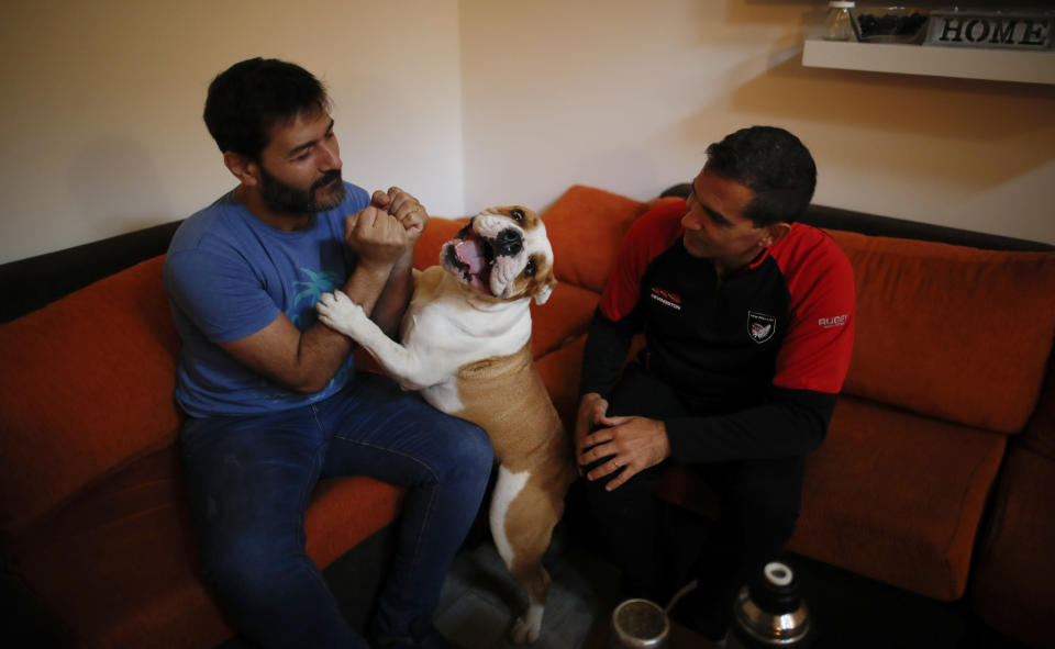 Former Catholic Priest Andres Gioeni, right, sits with his husband Luis Iarocci and their dog Boris after they got home from the bishopric where he started the process of apostasy in Buenos Aires, Argentina, Wednesday, March 17, 2021. Gioeni, who left the priesthood 20 years ago and married in 2014, said he has decided to formally leave the church after the Vatican decreed that the Catholic Church cannot bless same-sex unions since God 'cannot bless sin.' (AP Photo/Natacha Pisarenko)