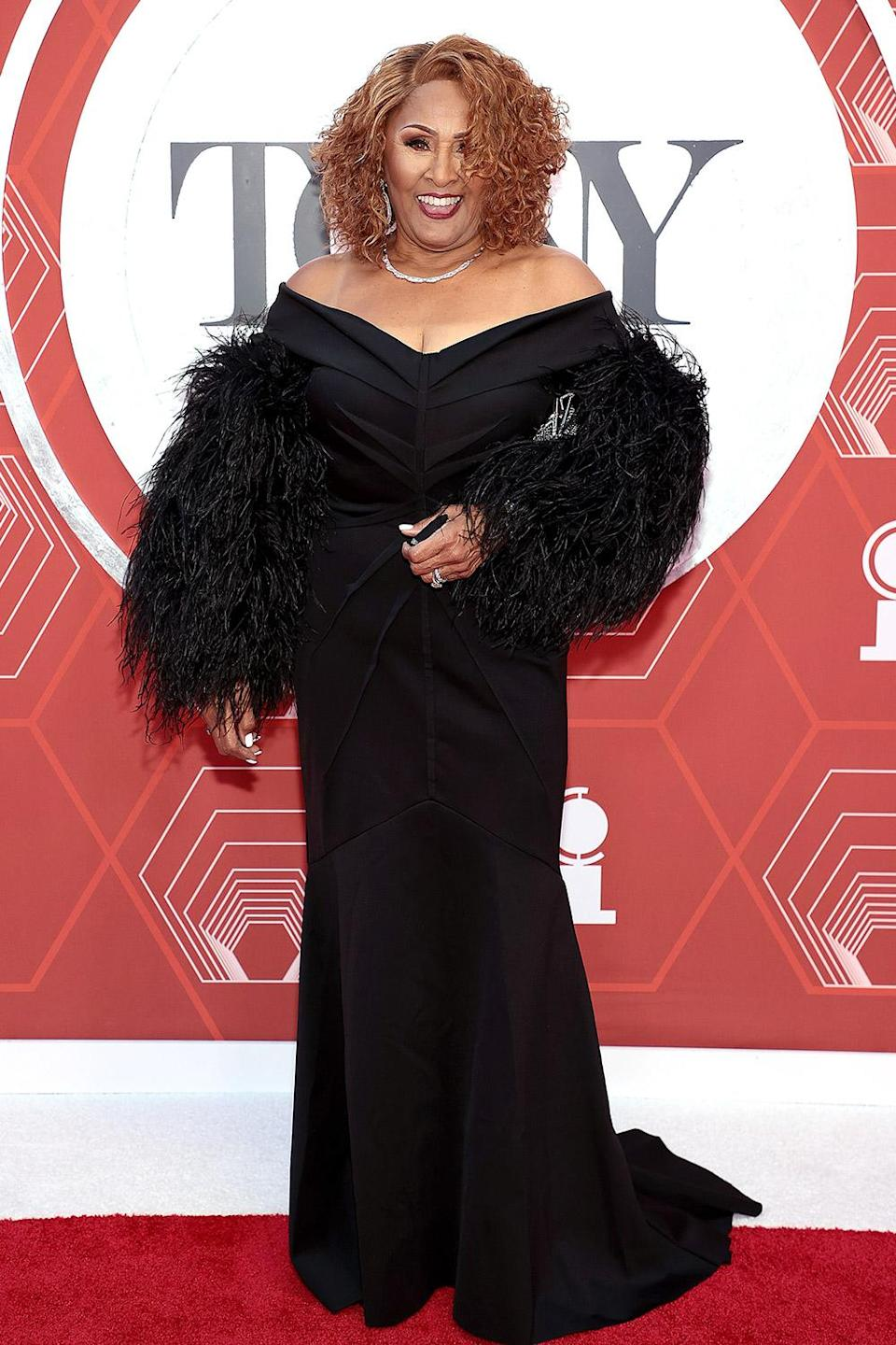 <p>Darlene Love looks glamorous in a black, feathered gown. </p>