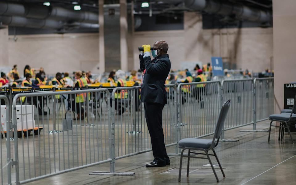 A poll watcher at a count in Philadelphia on November 3. The Trump campaign has claimed that observers were not permitted to view ballots being counted - BLOOMBERG