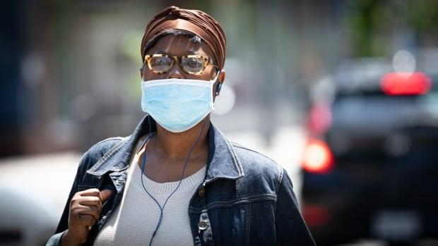A person wearing a mask walks Ottawa on a warm, sunny day in late June 2021. On Thursday, health officials in the nation's capital reported five new cases of COVID-19. (Brian Morris/CBC - image credit)