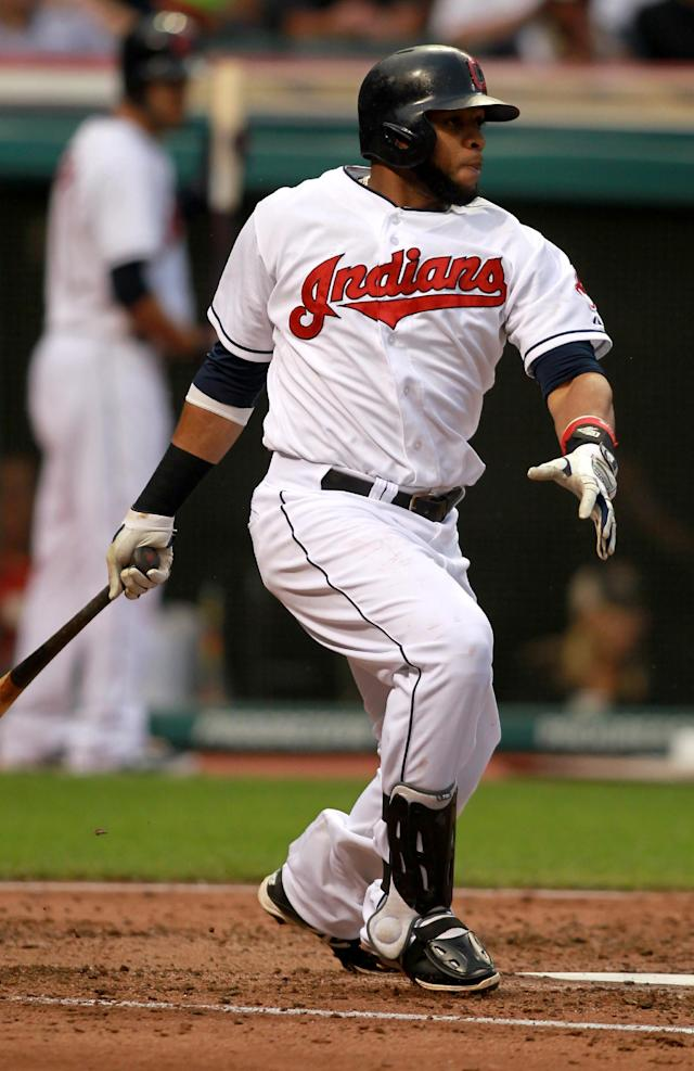Cleveland Indians' Carlos Santana follows through on an RBI single in the third inning of a baseball game against the Texas Rangers on Friday, Aug. 1, 2014, in Cleveland. (AP Photo/Aaron Josefczyk)