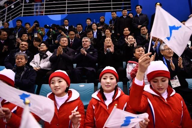 South Korea President Moon Jae-in and North Korean leader Kim Jong Un's sister Kim Yo Jong (right) sit behind North Korean cheerleaders as the unified Korea women's hockey team plays at the Winter Olympics. (Getty)