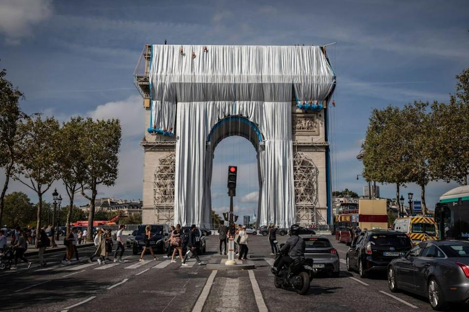 """<div class=""""inline-image__caption""""><p>Workers begin the process of wrapping up the Arc De Triomphe monument in silver-blue fabric on September 12, 2021.</p></div> <div class=""""inline-image__credit"""">Siegfried Modola/Getty</div>"""