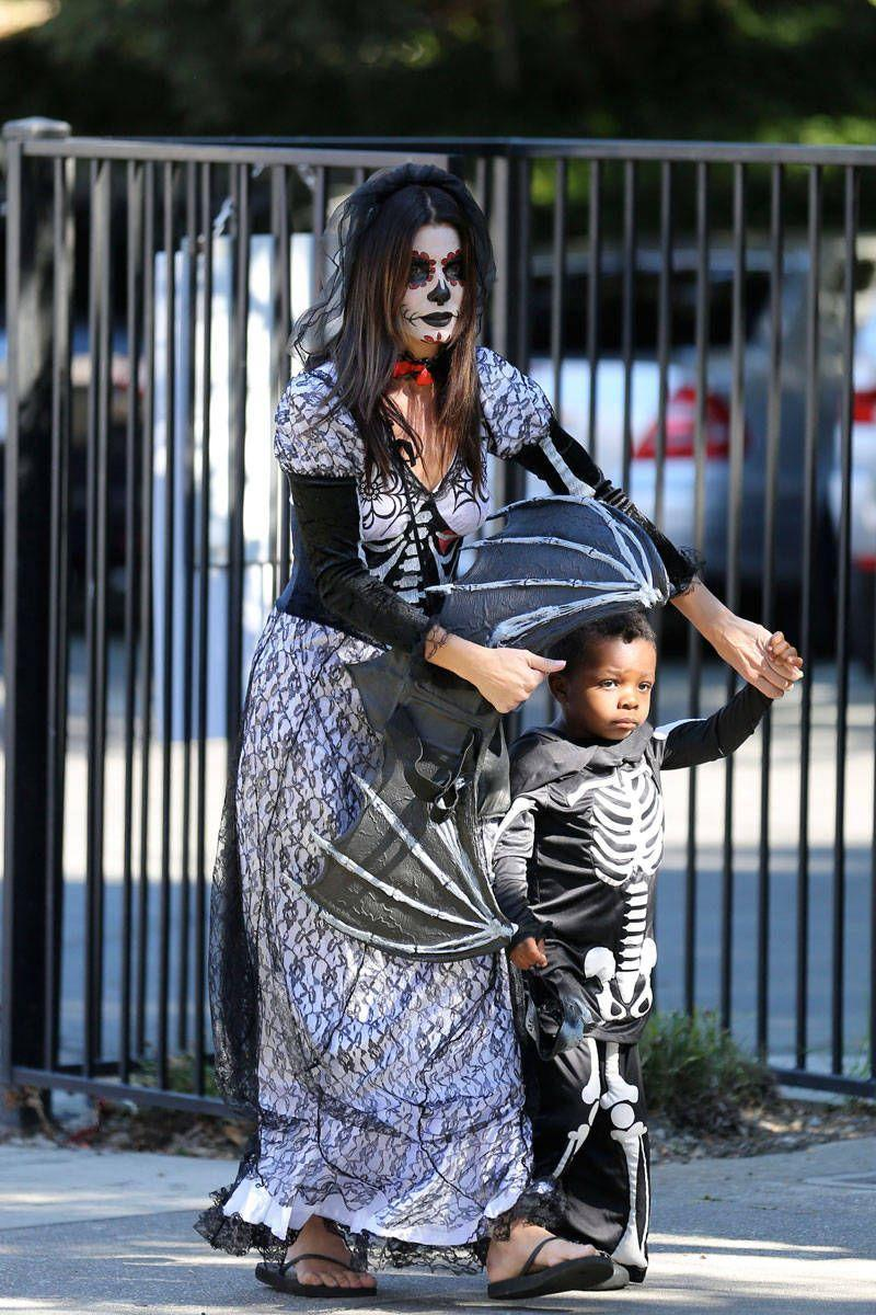 <p>In traditional Day of the Dead makeup while her son, Louis, puts on a skeleton costume.</p>